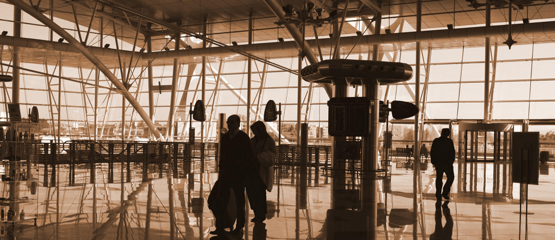 Three people walking through airport terminal.